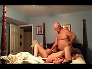Mature married couple experimenting with sex toys on four poster bed